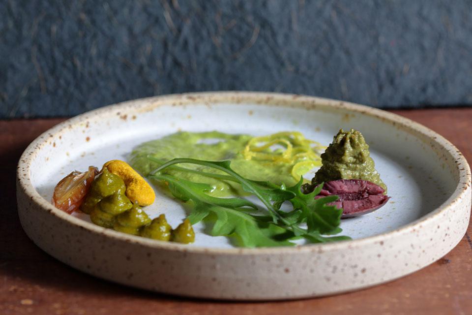 Die drei Pestosorten mit Rucola als Hauptbestandteil wurden auf einen runden Teller mit hoher Kante dekorativ, jeweils mit weiteren Zutaten, die im Pesto enthalten sind, beispielsweise dunkle Oliven, sowie einem Raukenblatt angerichtet.