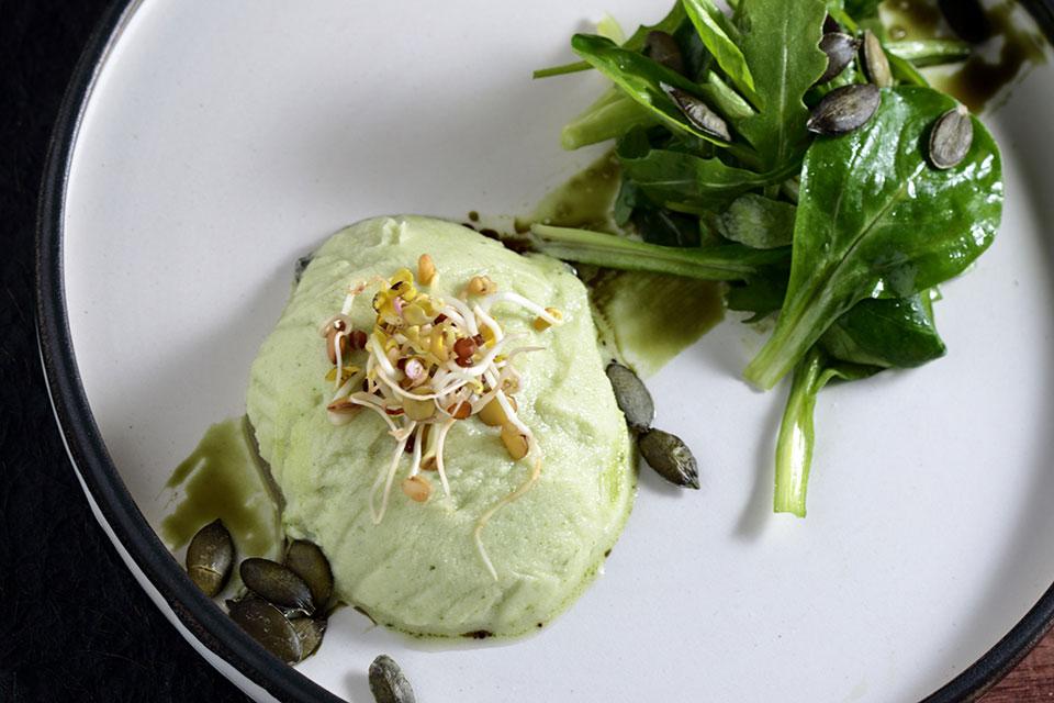Auf einem weißen Teller mit einem Bund frischer Rauke angerichtet, wird der Rucola-Frischkäse-Limetten-Taler mit mariniertem Gemüse, zubereitet von Estella Schweizer, zusätzlich mit frischen Sprossen garniert und sieht dadurch besonders appetitlich aus.