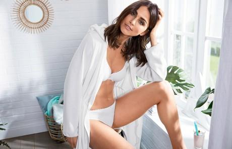 Eine Frau in weißer Wäsche und mit einem leichten, weißen Morgenmantel aus der nachhaltigen Kollektion von Tchibo bekleidet und sitzt an einem Fenster.