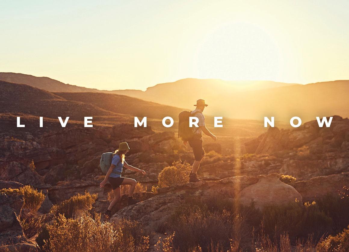 Auf dem Kampagnenbild des spanischen Herstellers Buff wandern ein Mann und eine Frau, die nur schemenhaft zu erkennen sind, durch eine weite, bewachsene Landschaft, während im Hintergrund die Sonne untergeht.