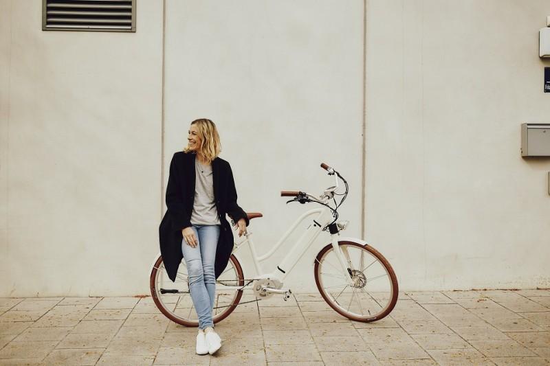 Eine junge blonde Frau steht mit ihrem weißen E-Bike von Ego Movement vor einer hellen Wand.