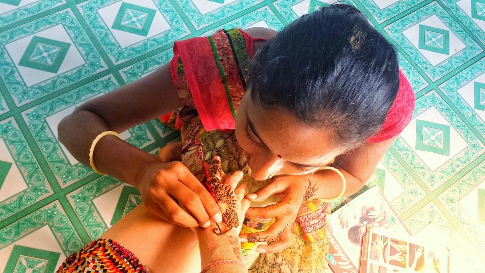 Eine Inderin bemalt eine Hand mit Henna