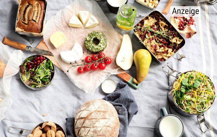 Käse, frisches Gemüse, Obst und Brot sind auf einer Picknick-Decke ausgebreitet und bereit für den Verzehr.