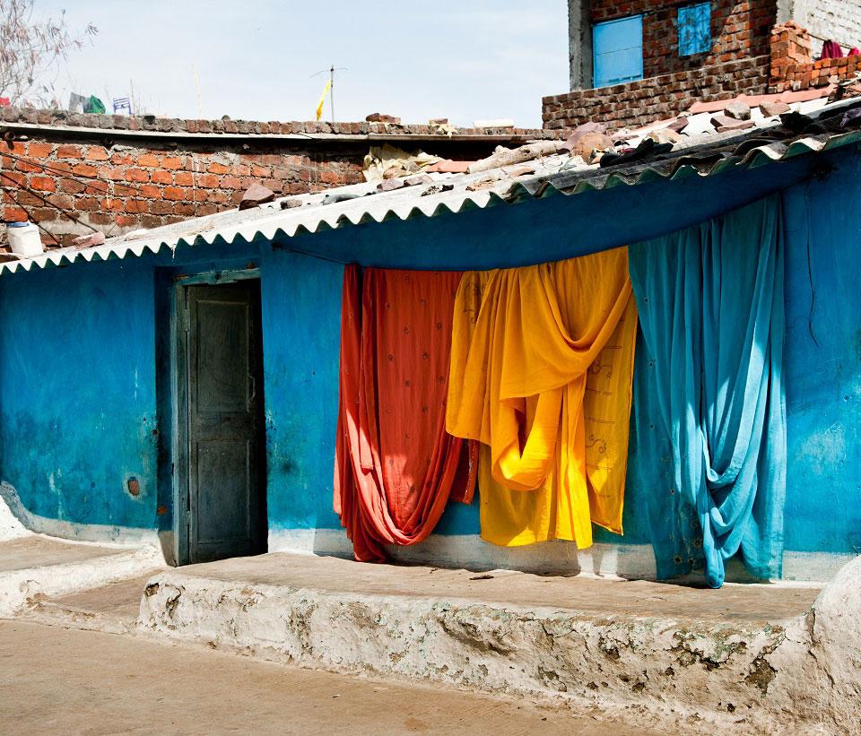Indische Seidenstoffen hängen vor der blauen Wand eines indischen Hauses