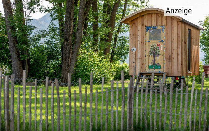 Bauwagen des Montessori-Kindergartens auf grüner Wiese in der Wohnanlage Dahoam im Inntal