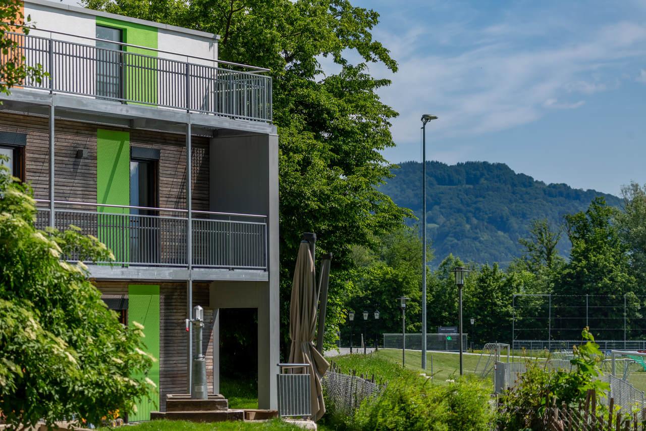 Ein zweistöckiges Wohnhaus mit Bergen im Hintergrund.