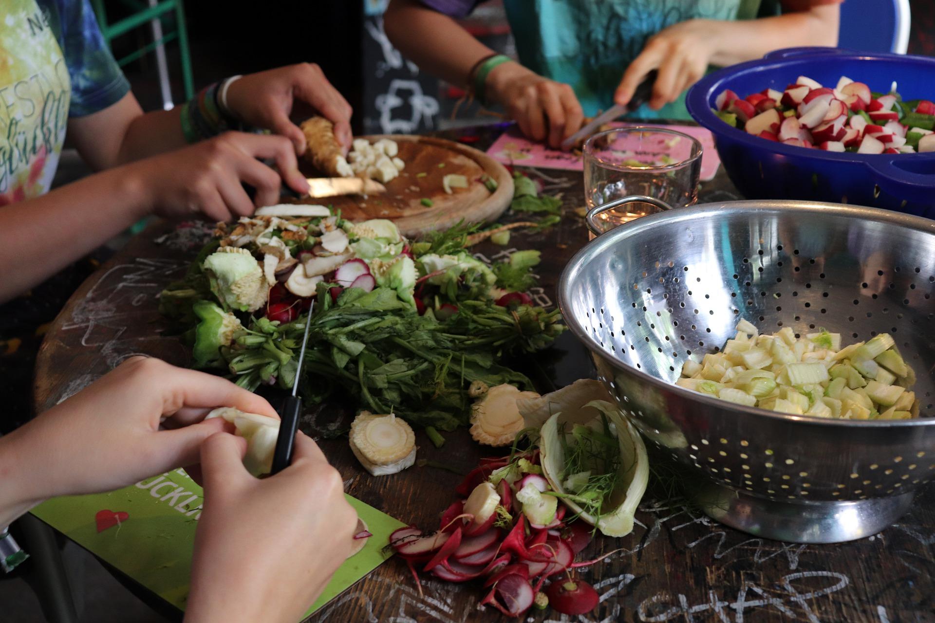 Drei Personen schneiden Gemüse für eine nachhaltige Ernährung.