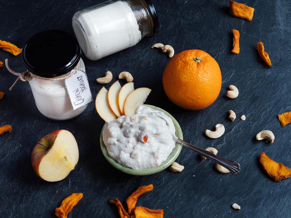 Veganer Joghurt aus Cashews, angerichtet mit Apfel, Orangen und ganzen Nüssen.