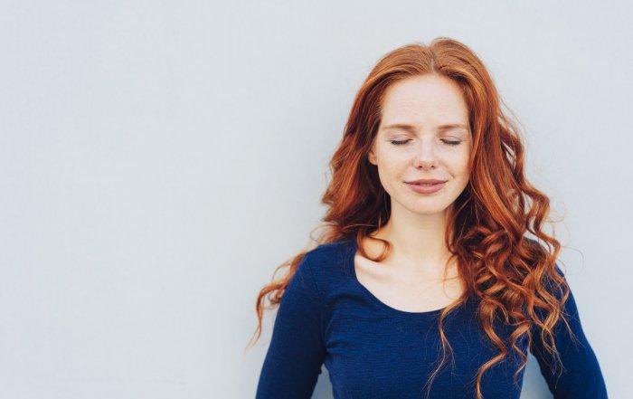 Junge Frau mit rotem Haar genießt die positive Wirkung von CBD mit geschlossenen Augen
