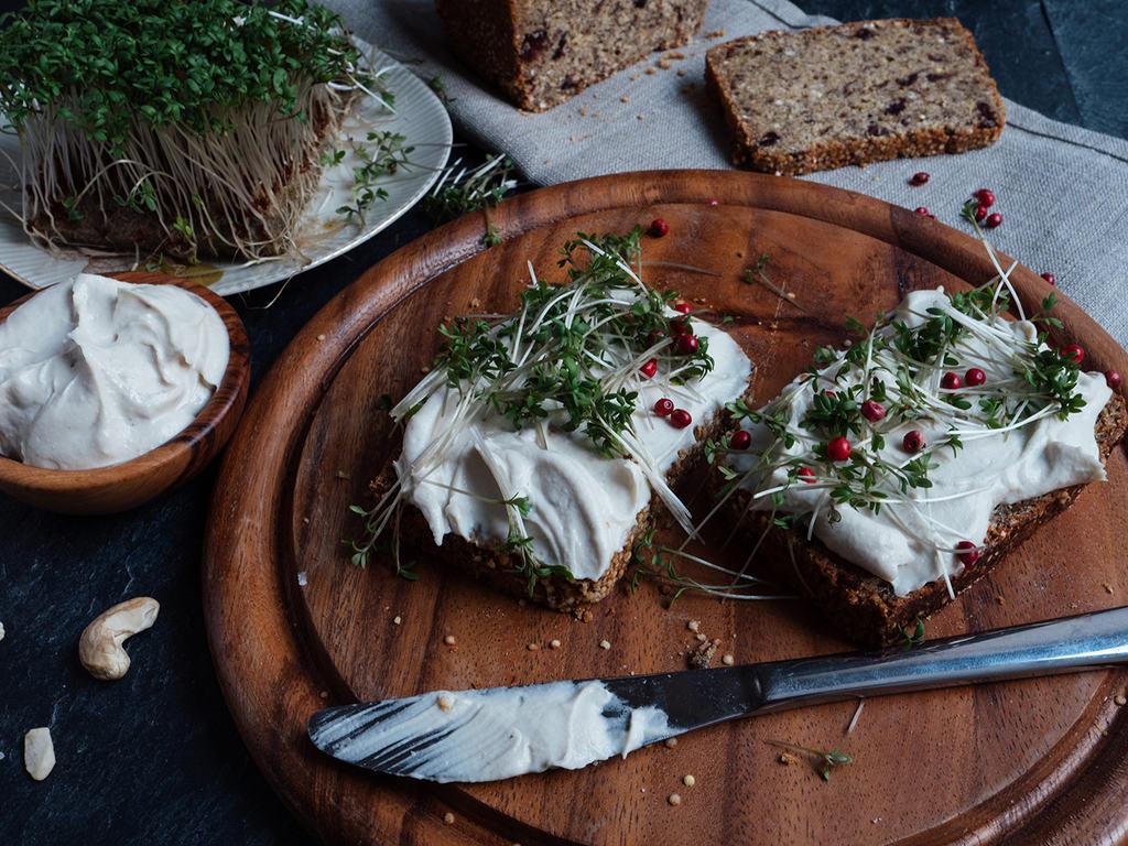 veganer Frischkäse aus Cashewmilch auf einem Vollkornbrot mit Kräutern garniert.