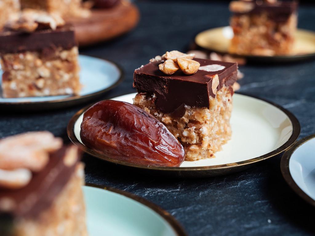 Ein Stück veganer Erdnuss-Schokoriegel auf einem Teller mit einer Dattel.