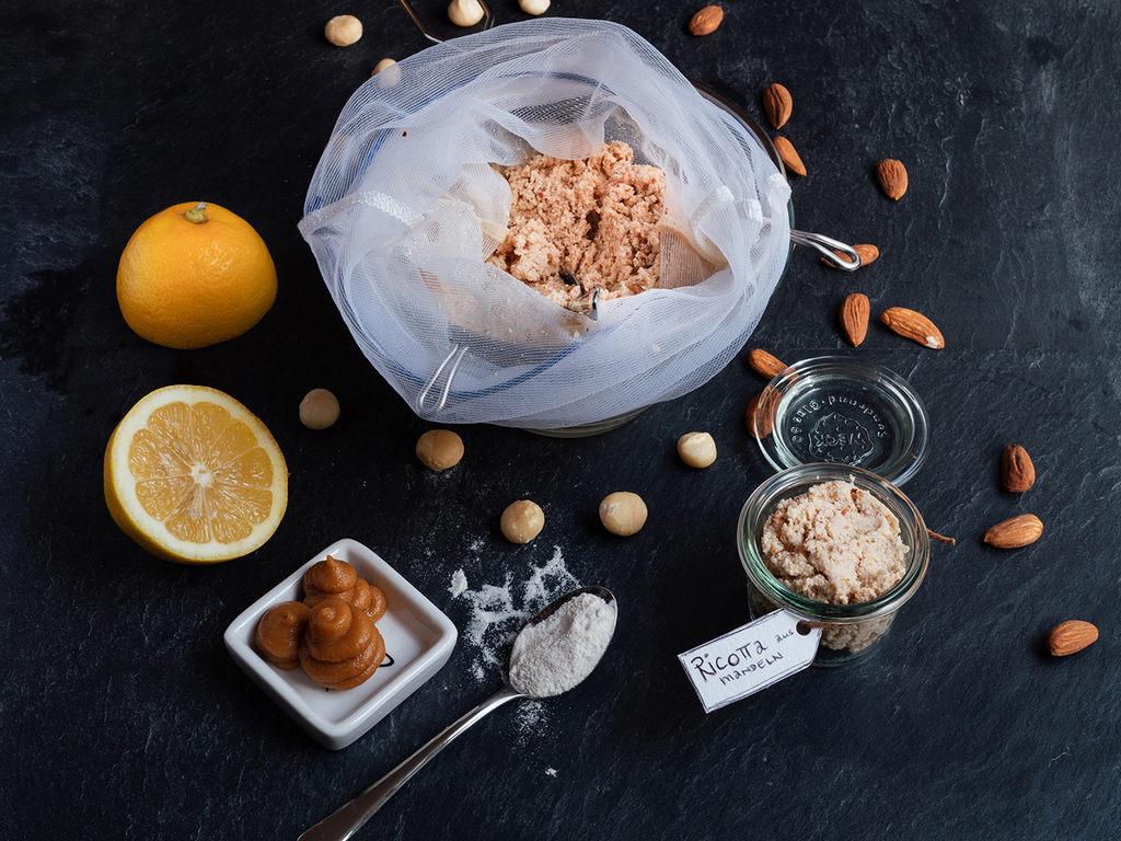 Veganer Ricotta aus Mandeln in einem Glas und in einem Nussmilchbeutel, den man für die Zubereitung benötigt.
