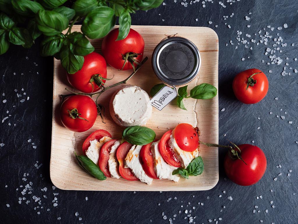 Mozzarella, vegan aus Nüssen, auf einem Holzteller mit Tomaten und basilikum als Caprese angerichtet.