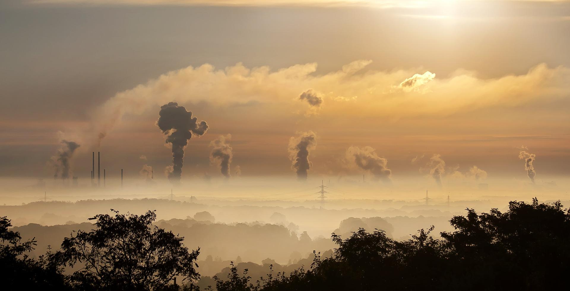 Industrieschornsteine im Dunst symbolisieren den CO2-Ausstoß als Ursache für die Klimakrise.