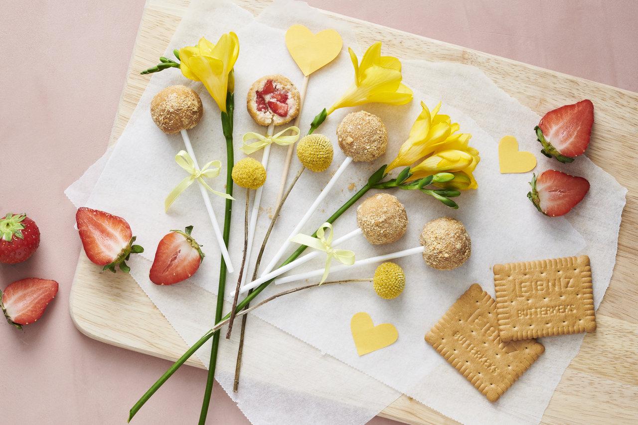 Leibniz Buttekekse liegen mit Erdbeeren und Strawberry Cheesecake-Pops sowie gelben Blumen auf dem Tisch