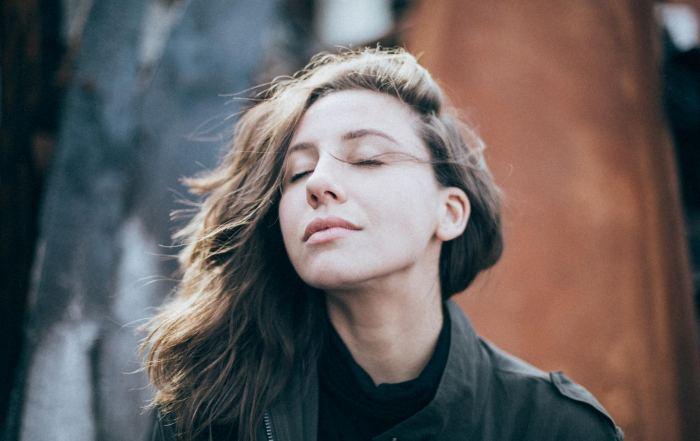 Junge Frau mit geschlossenen Augen und entspanntem Gesichtsausdruck.
