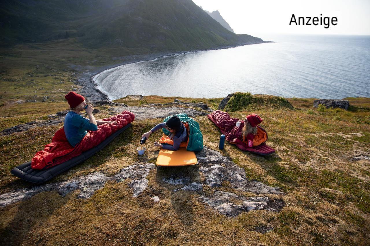 Drei Personen liegen in Schlafsäcken von Deuter in der Natur mit Blick auf einen See