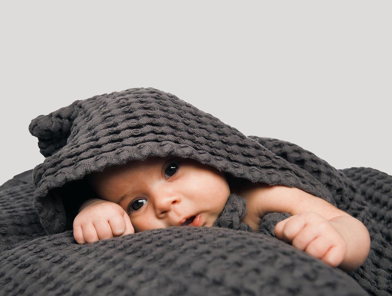 Baby in einem dunkelgrauen Handruck mit Waffelmusterprägung