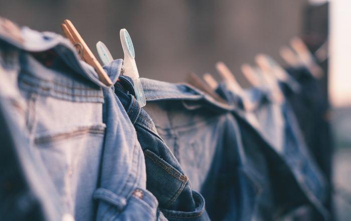 Nachhaltige Klamotten in Jeans-Optik trocknen auf einer Wäscheleine