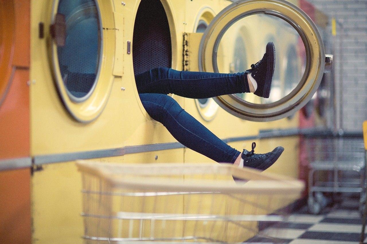 In einem Waschsalon sieht man die Beine einer Person, die in eine gelbe Waschmaschine geklettert ist.