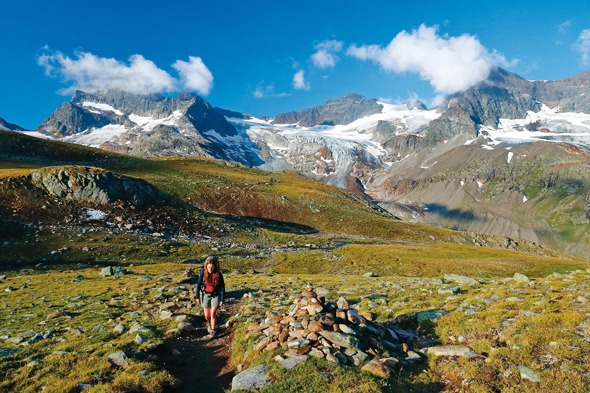 Wanderin in einer grünen Ebene mit Bergpanorama im Hintergrund