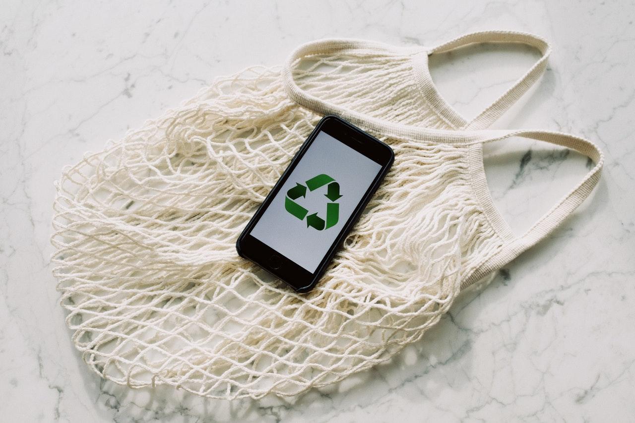 Smartphone zeigt grünes Recycling-Symbol und liegt auf einem nachhaltigen Einkaufsnetz