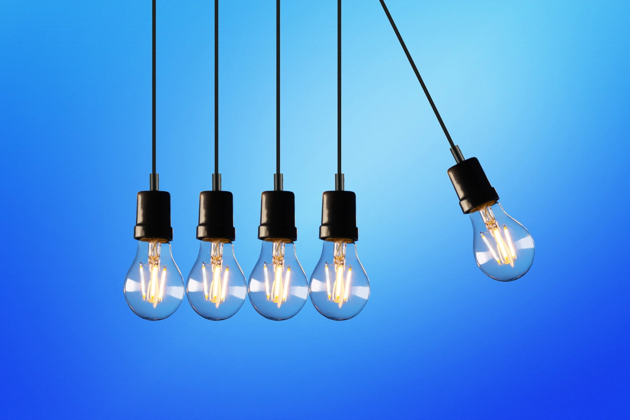 Eine LED-Leuchte schwingt auf weitere vier Leuchten wie im physikalischen Kugelpendel von Newton und symbolisiert den eigenen Einfluss auf den Umweltschutz und die Auswirkung des Energiesparens.