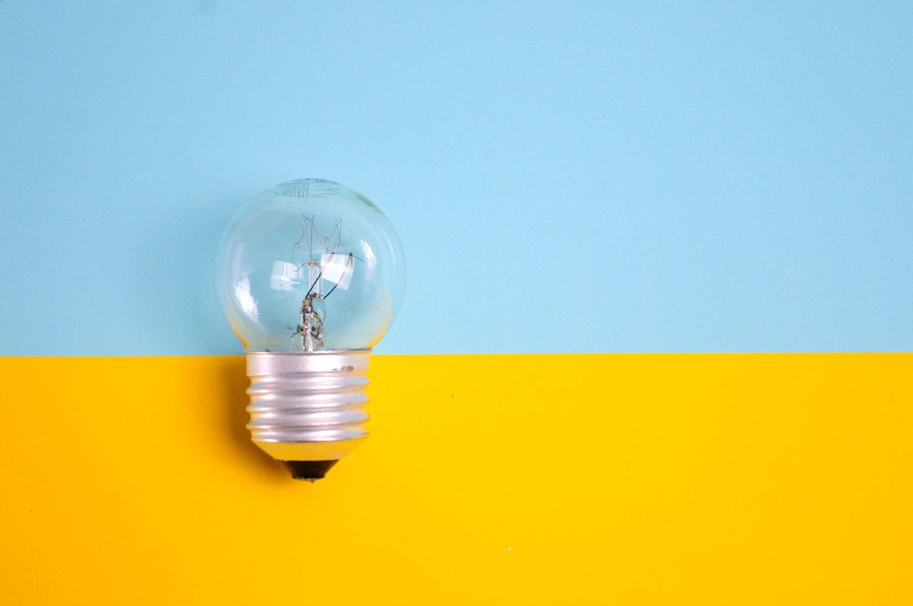 Glühbirne aus blau-gelben Untergrund symbolisiert Stromsparen in nachhaltigen Unternehmen