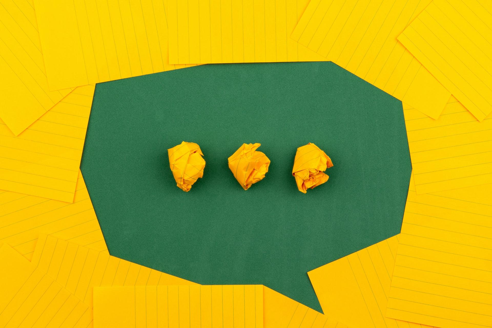 Aus gelben Notizzetteln auf grünem Grund geformte Sprechblase mit drei Punkten symbolisch für ein Umdenken Richtung nachhaltige Unternehmenskultur