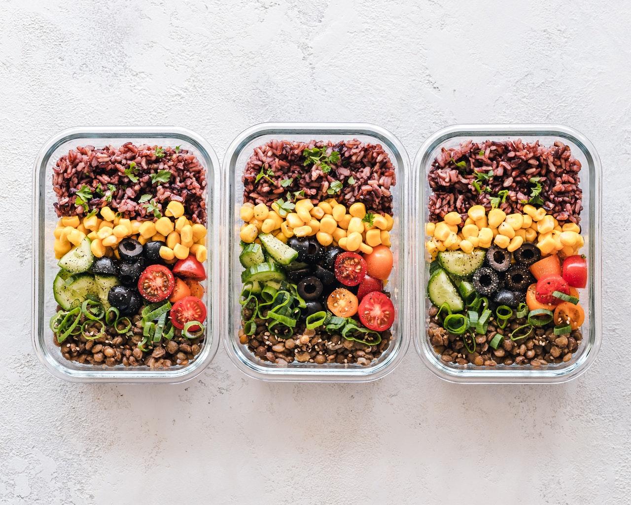 Drei Frischhaltebehälter aus Glas sind mit frischem Gemüse, Reis und Nüssen gefüllt.