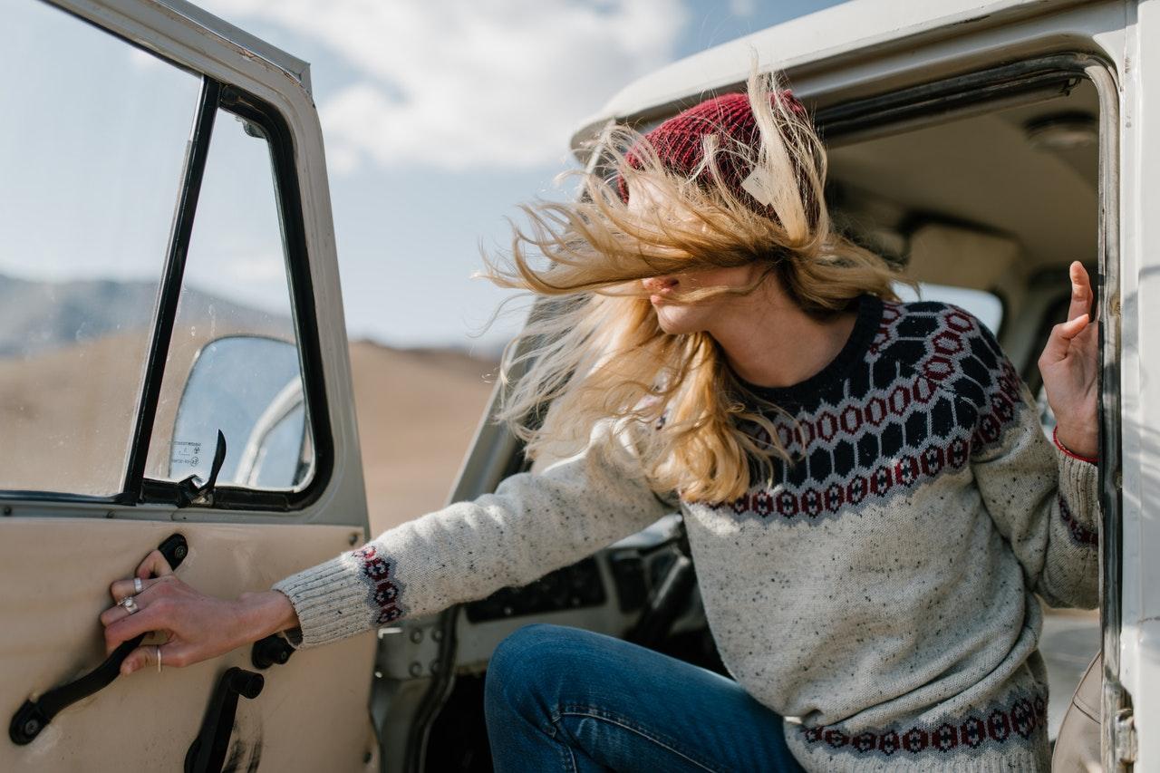 Frau mit wehenden blonden Haaren öffnet eine Autotür