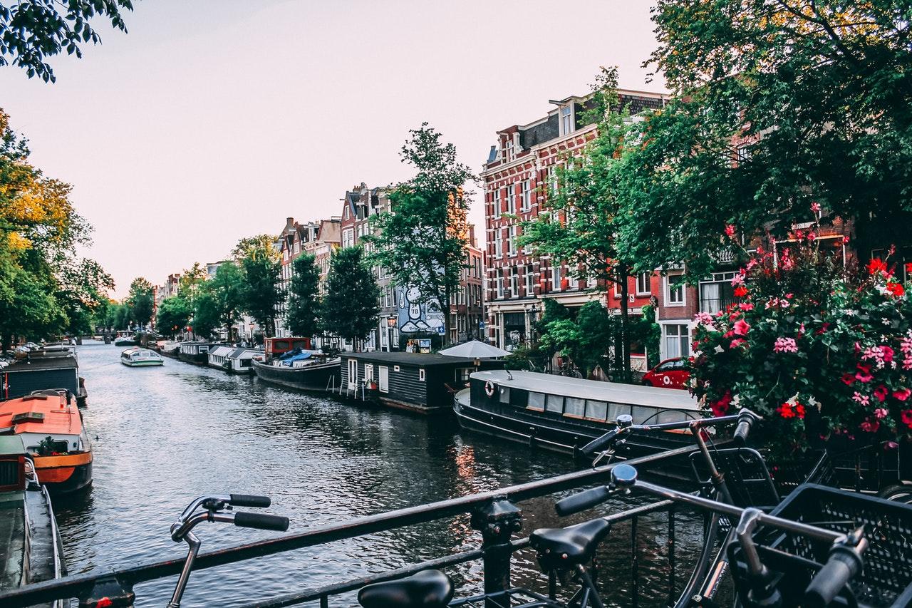 Blick von einer Brücke in Amsterdam mit Fahrrad am Geländer aufs Wasser