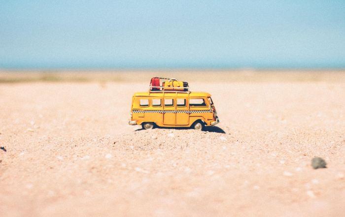 Gelber Spielzeug-Campervan im Sand am Strand symbolisch für Urlaub