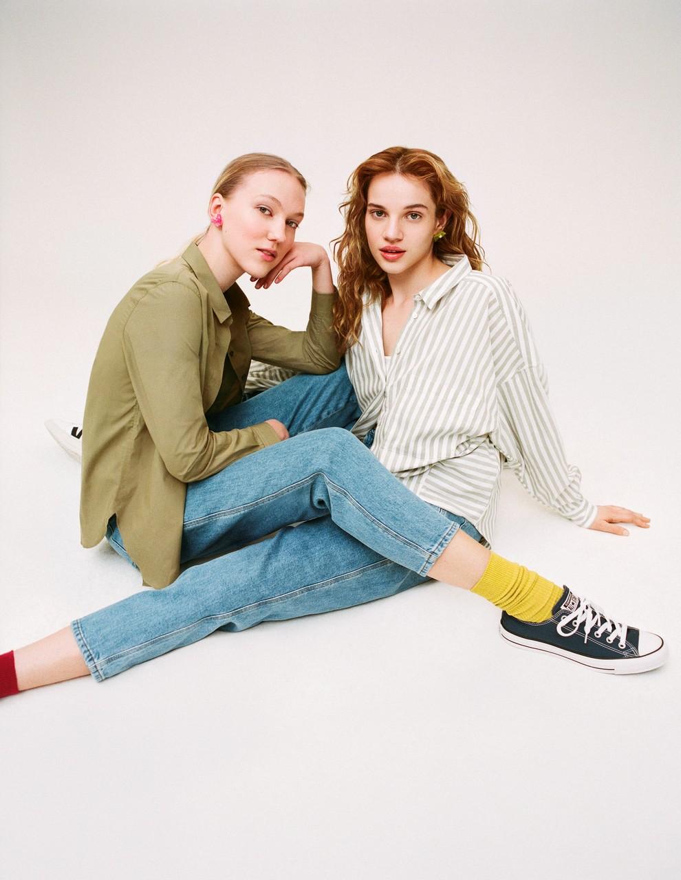 Zwei Frauen in fair produzierter Fashion von Closed sitzen mit überschlagenen Beinen auf dem Boden.
