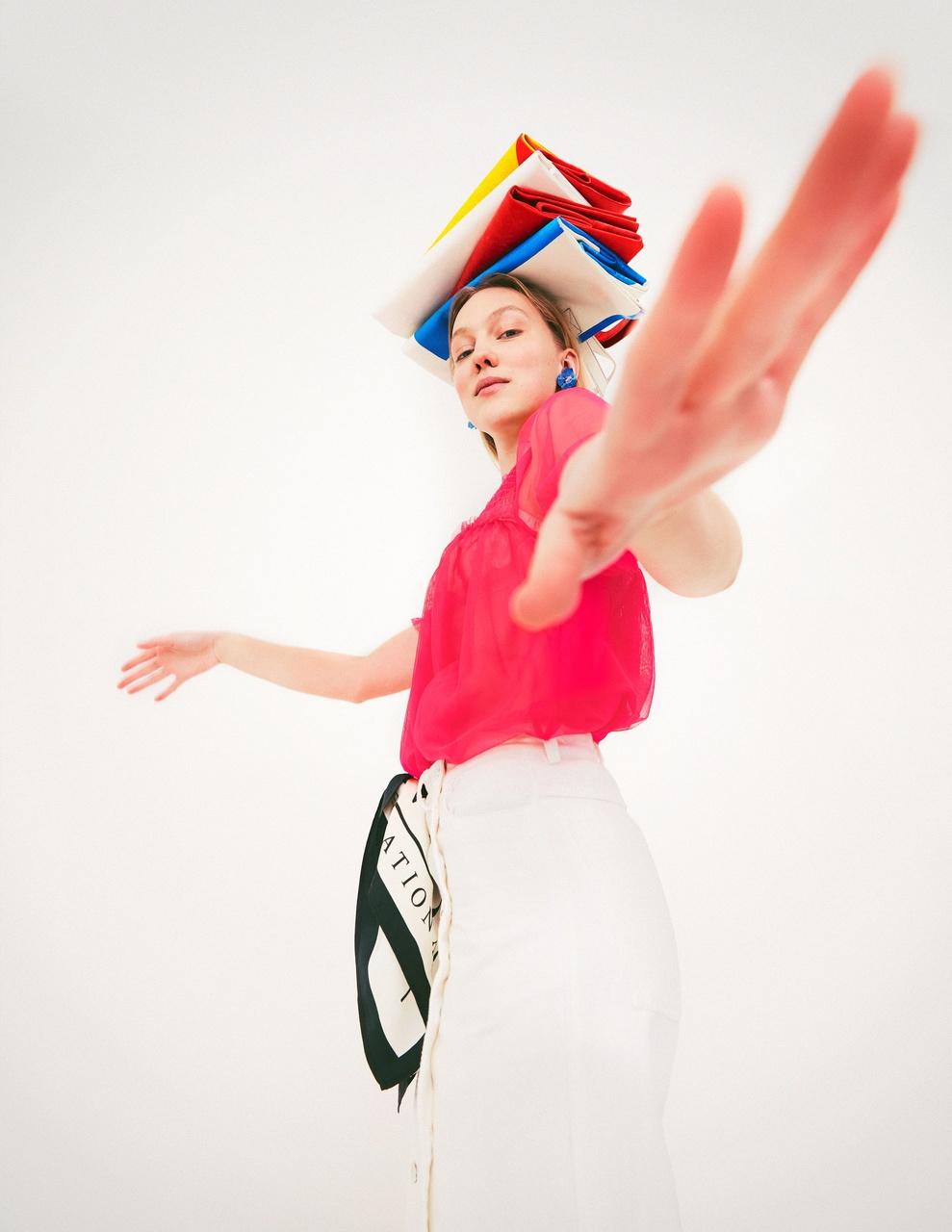 Frau mit nachhaltiger Kleidung balanciert Bücher auf ihrem Kopf und Blick dabei seitlich in die Kamera