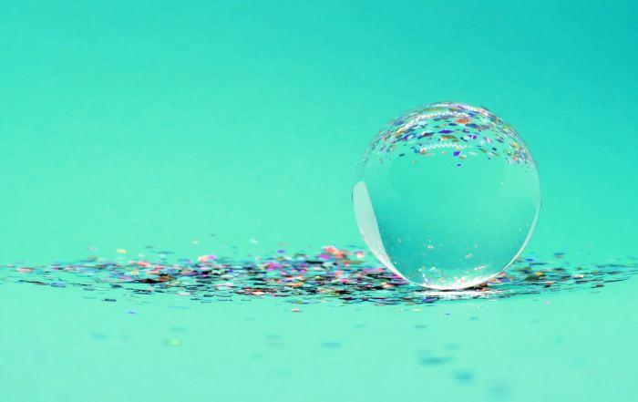 Glaskugel auf Glitzerpartikelchen, die sich in der Kugel spiegeln, symbolisieren Miroplastik in unserer Umwelt.
