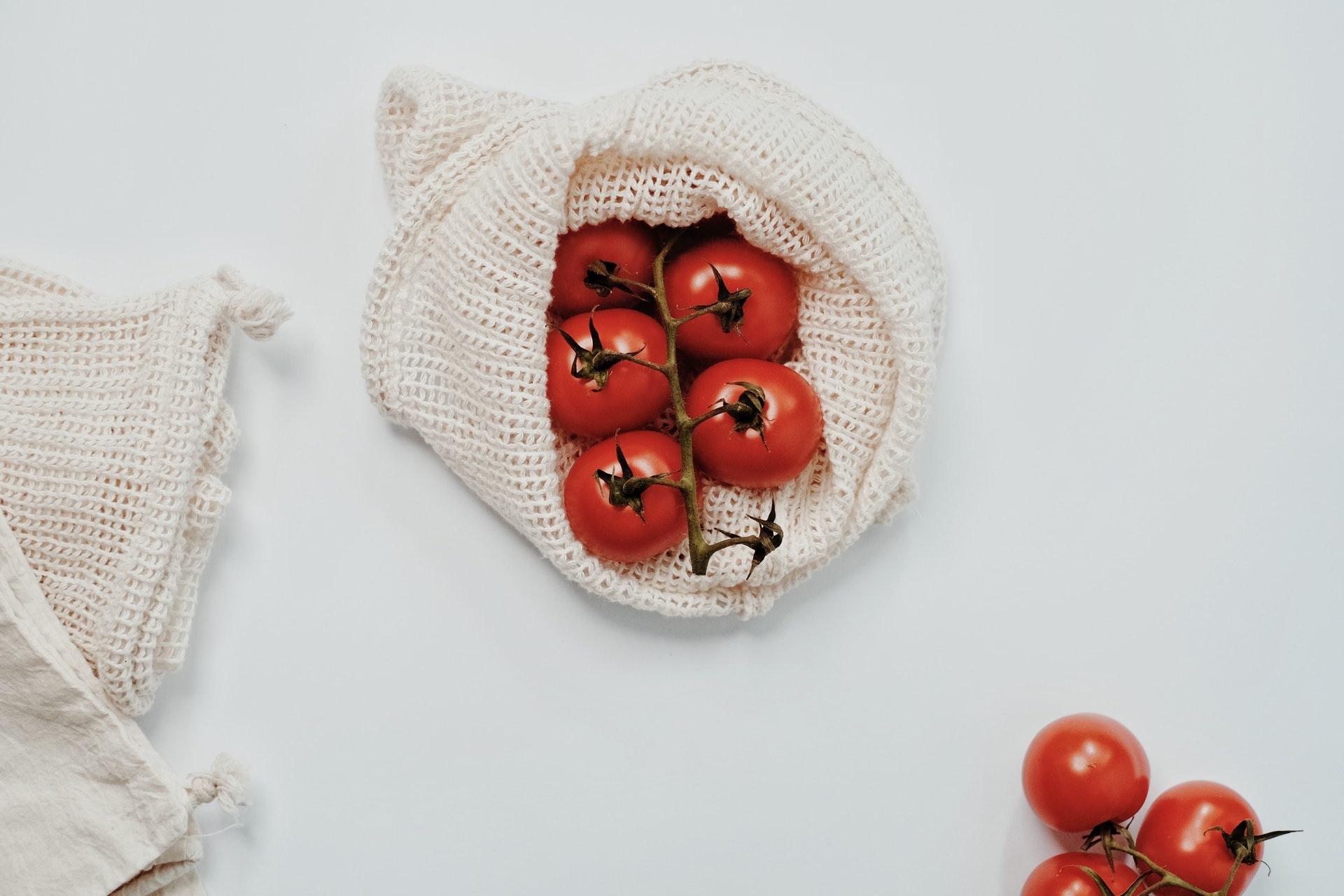 Rote Tomaten in weißem Baumwoll-Frischenetz auf weißem Grund als Beispiel für nachhaltigen Einkauf.