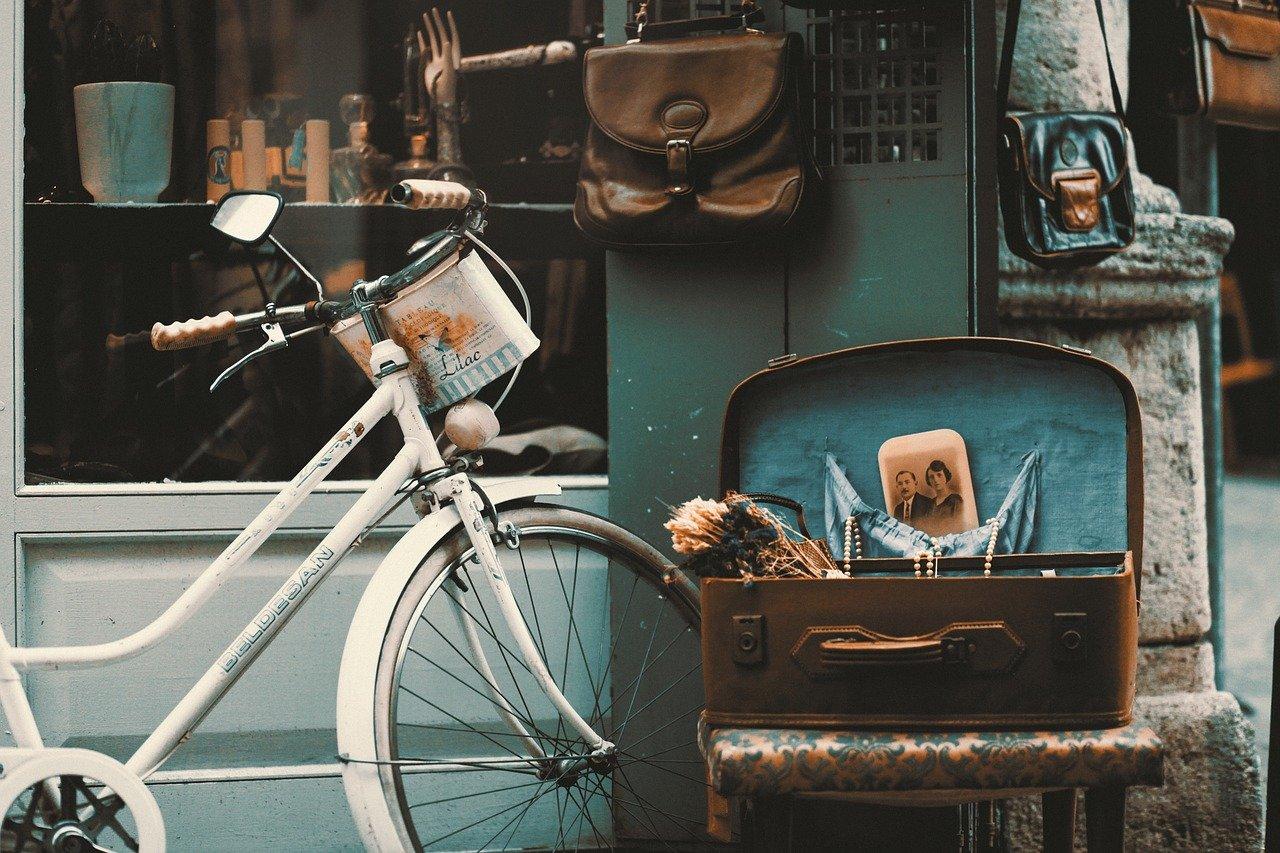 Vor einem Secondhand-Shop sind Fahrrad,Koffer, Tasche und Deko-Artikel einladend arrangiert.