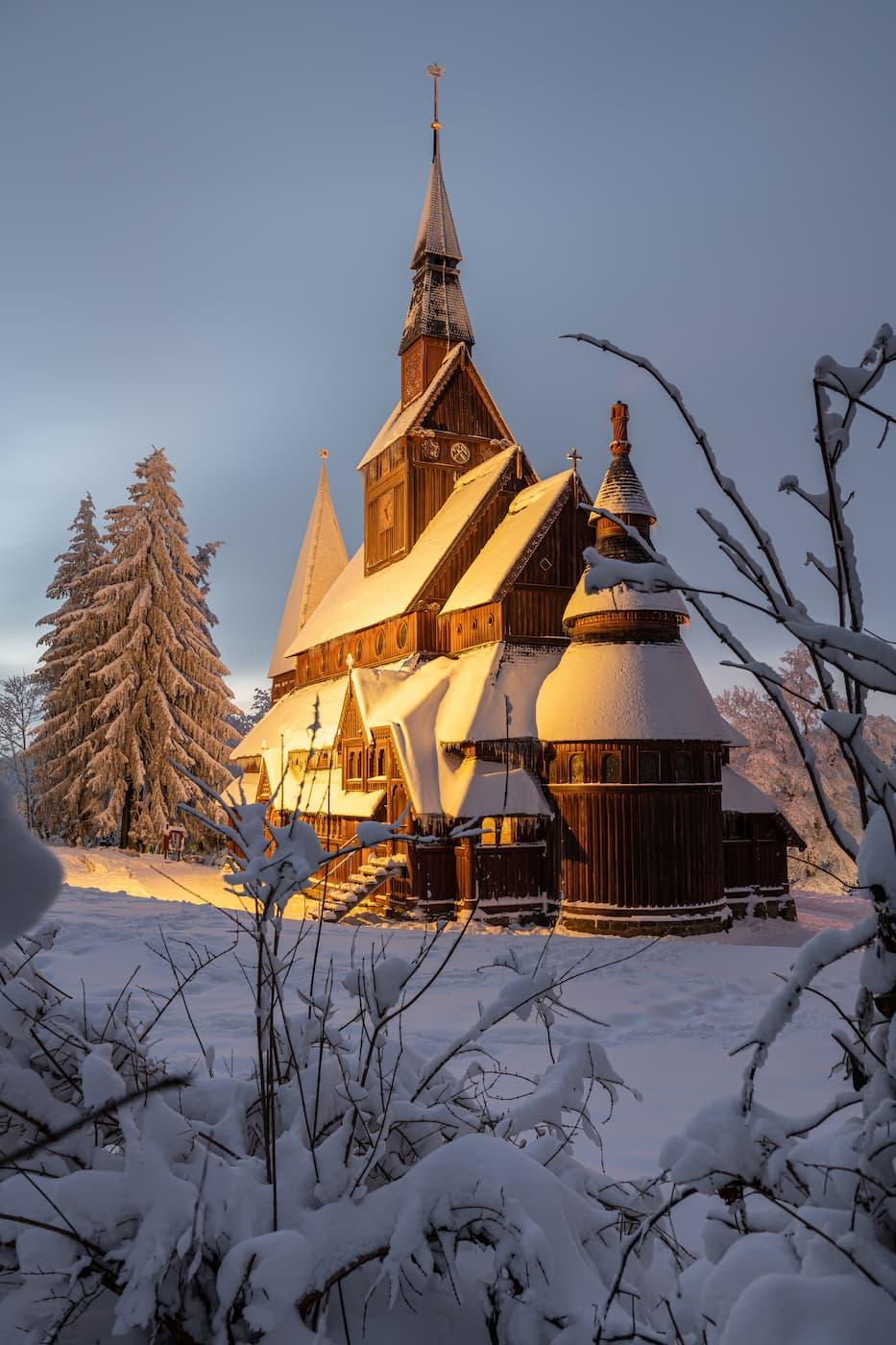 Die mit Schnee bedeckte Stabkirche im Harz in Niedersachsen im goldfarbenen Abendlicht.