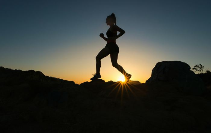 Frau joggt bei Sonnenuntergang über Steine
