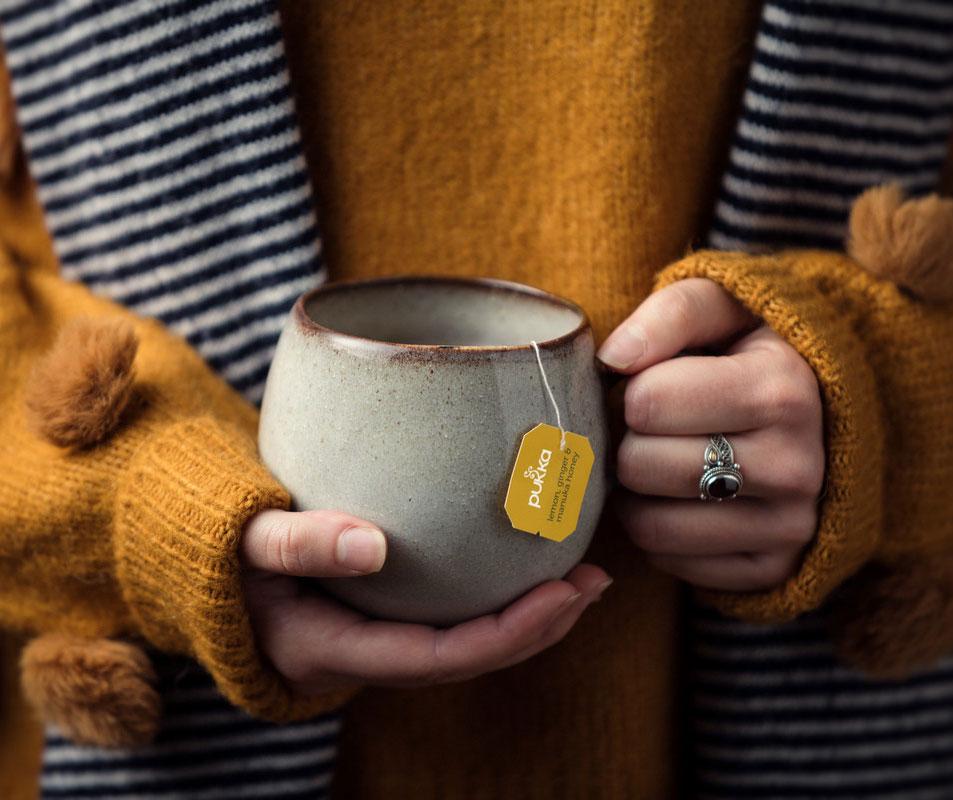 Eine Frau wärmt sich ihre Hände an einer Teetasse, gefüllt mit der Sorte Lemon Ginger Manuka Honey von Pukka Tee.