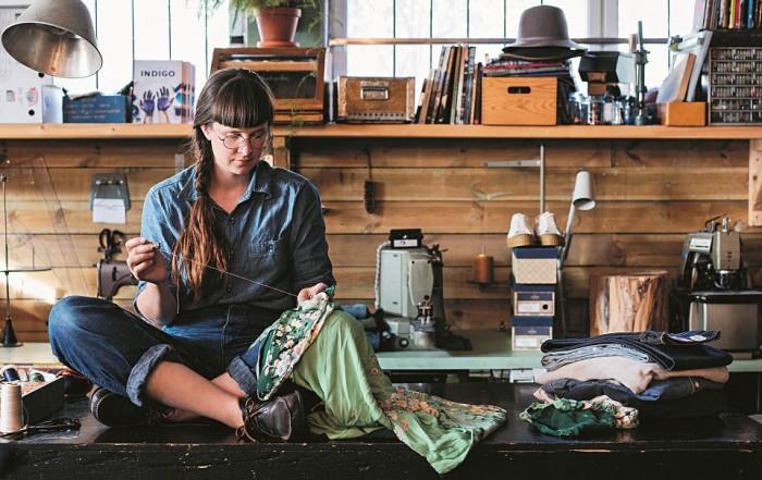 In einer Werkstatt sitzt die Autorin und Schneiderin Kerstin Neumüller im Schneidersitz auf einem Tisch und näht mit Nadel und Faden an einer mintfarbenen Jacke.