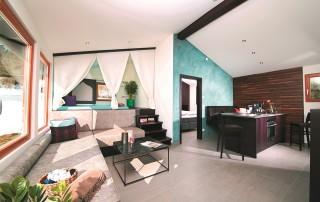 Vom Wohnraum des Chalets kommt man in einen offenen Schlafbereich, der optional durch einen Vorhang abgetrennt werden kann, sowie in das Badezimmer mit Regendusche.
