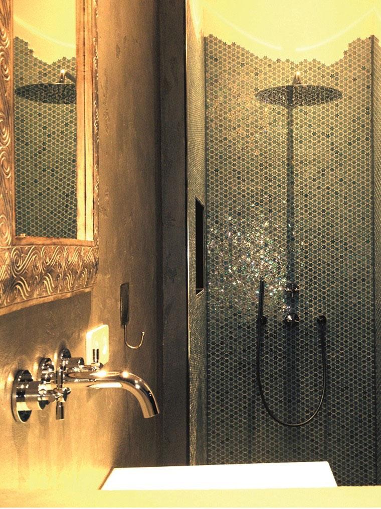 Das Badezimmer mit Regendusche im 7 Sentidos wirken durch die goldfarbene Wandfarbe, die gold-glänzenden Amaturen und gold-schimmernden Mosaiksteinchen besonders luxuriös.
