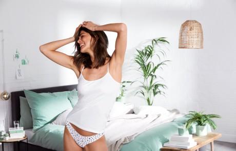 Eine Frau, bekleidet mit einem weißen Spaghettitop und einem weißen Slip, tanzt durch ihr Schlafzimmer.