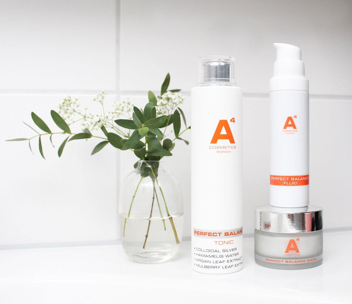 Pflegeprodukte von A4 in einem Badezimmer mit weißen Blumen in eienr Vase