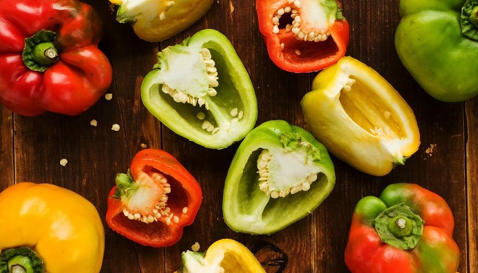 Auf einem Holztisch liegen mehrere Paprika – teils aufgeschnitten, teils im Ganzen – und präsentieren die bunte Farbvielfalt der Paprikaschoten von Rot, Grün und Gelb sowie den Farbkombinationen und Nuancen dieser Farben.