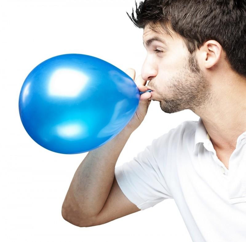 Mann bläst Luftballon auf