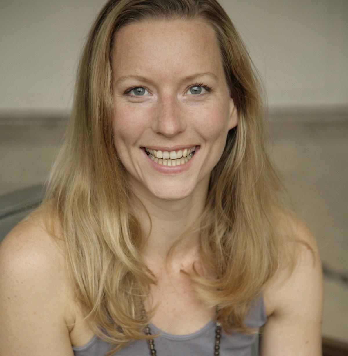 Die blonde Yoga-Lehrerin Antje Schäfer trägt ein graues Top und lächelt.