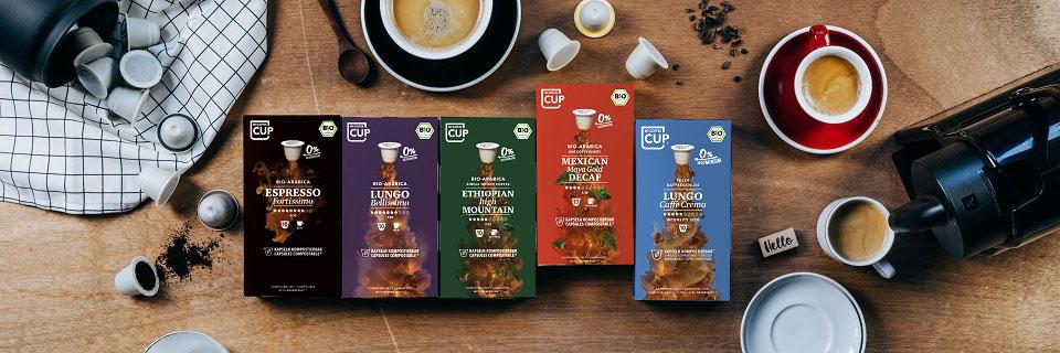 Fünf von acht aromatischen Sorten der nachhaltigen Kaffeemarke Unicaps liegen aufgereiht auf einem Tisch inmitten gefüllter Kaffeetassen, die von oben fotografiert wurden, und stehen für die Vielfalt des Start-ups.